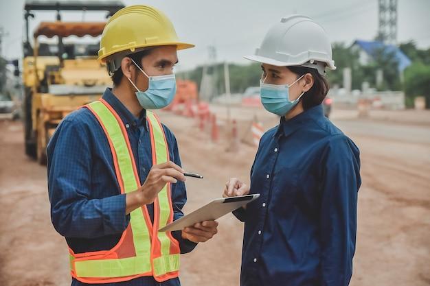 Arbeiter ingenieur tragen maske, die durch tablette auf straßenbau vor ort arbeitet