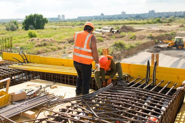 Arbeiter installieren beim bau einer transportbrücke bewehrungsstrukturen auf der schalung