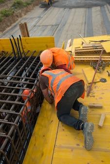 Arbeiter installieren bewehrungsstrukturen auf der schalung, bevor sie beton gießen