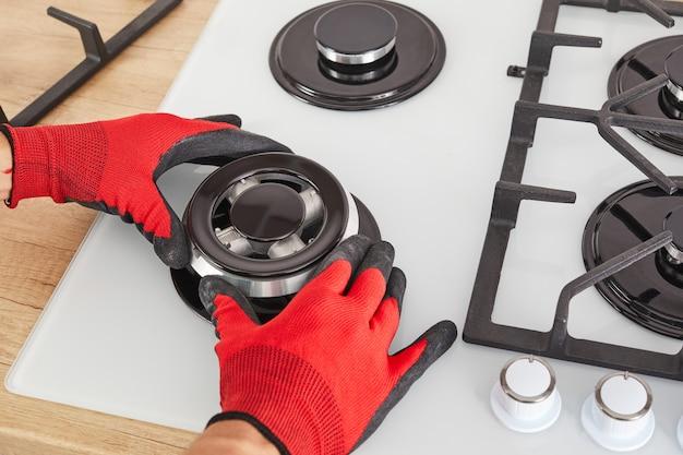Arbeiter installieren brenner auf gasherd im kücheninneren. reparaturen des gasbedienfeldes.