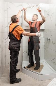 Arbeiter installieren glastür der duschkabine.