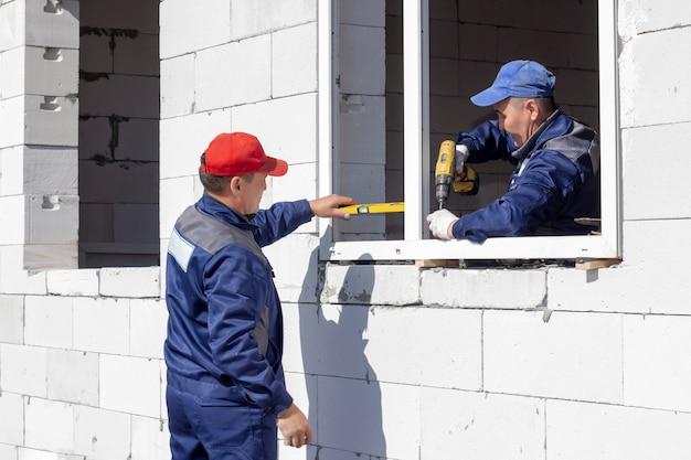 Arbeiter installieren verglasungen in einem im bau befindlichen haus