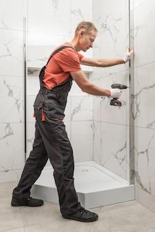 Arbeiter installiert ein metallprofil der duschkabine mit einem schraubendreher.