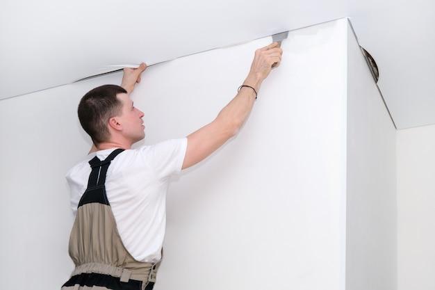 Arbeiter installiert eine spanndecke. bau- und sanierungskonzept