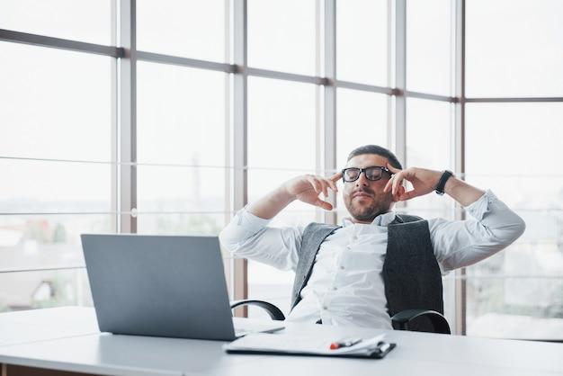 Arbeiter ist ein junger mann mit einem laptop im büro