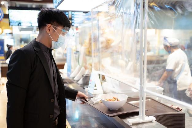 Arbeiter kaufen sie lebensmittel im einkaufszentrum. er trägt ein mess and face shield, um sich vor viren zu schützen.