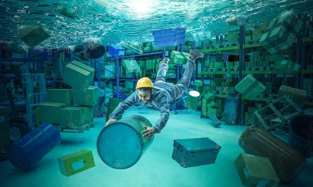 Arbeiter klammert sich an einen mülleimer in einem völlig überfluteten lagerhaus.