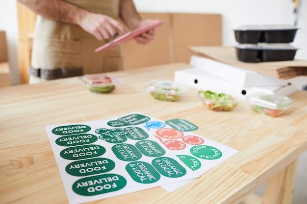 Arbeiter kleben etiketten und verpackungsaufträge im lebensmittel-lieferservice