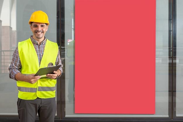 Arbeiter lächelnd mit einer akte und einer gelben weste mit einem roten poster im rücken