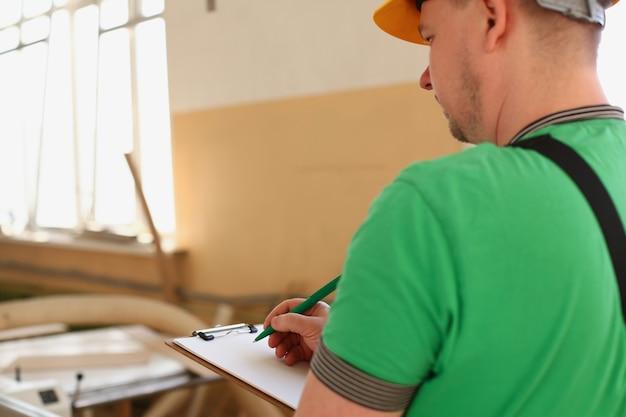 Arbeiter macht notizen in der zwischenablage mit grüner stift nahaufnahme.
