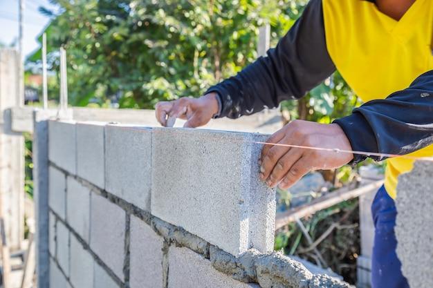 Arbeiter mauerwerk bauen wände mit zementblöcken und mörtel, indem sie in schichten aufbauen.