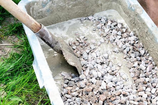 Arbeiter mischen, rühren zementschlamm, betonschuttmörtel mit schaufel in großer schüssel, reservoir, trog, eimer. vorbereitung für den bauprozess, renovierung, fundament legen.