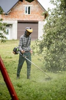 Arbeiter mit einem gasmäher in der hand, der gras vor dem haus mäht. trimmer in den händen eines mannes. gärtner, der das gras schneidet. lebensstil.