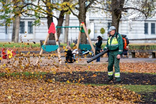 Arbeiter mit einem gebläse reinigt einen rasen im stadtpark und bläst herbstlaub weg