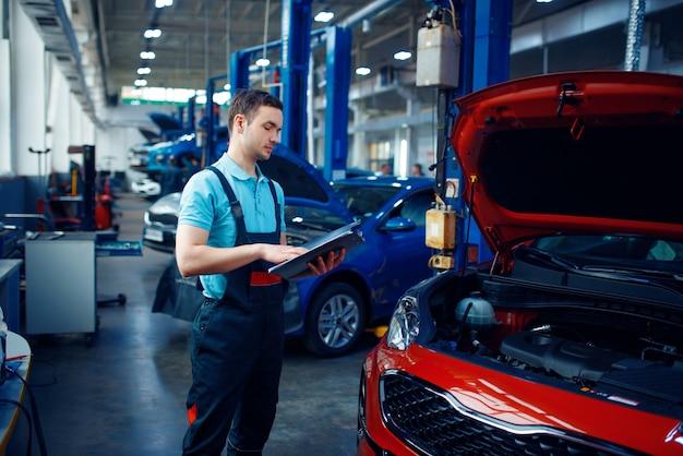 Arbeiter mit einer checkliste steht am fahrzeug mit geöffneter motorhaube, autotankstelle. überprüfung und inspektion von kraftfahrzeugen, professionelle diagnose und reparatur