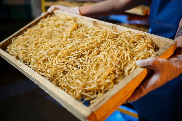 Arbeiter mit einer schachtel nudeln. das mädchen arbeitet an der herstellung von spaghetti. nudeln machen. teigwarenfabrik.