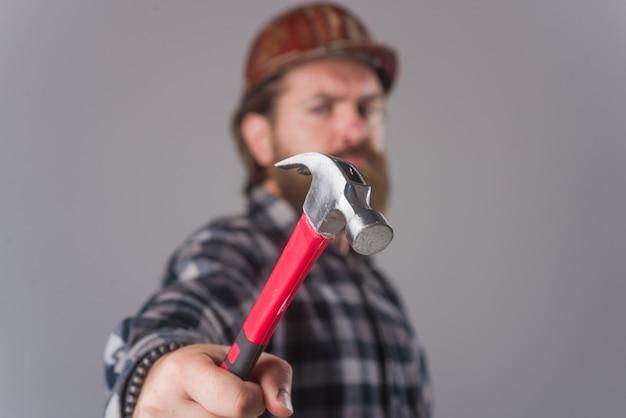 Arbeiter mit hammer. bärtiger mann mit hammer in den händen. bärtiger arbeiter. porträt des mannes mit hammer. arbeiter.