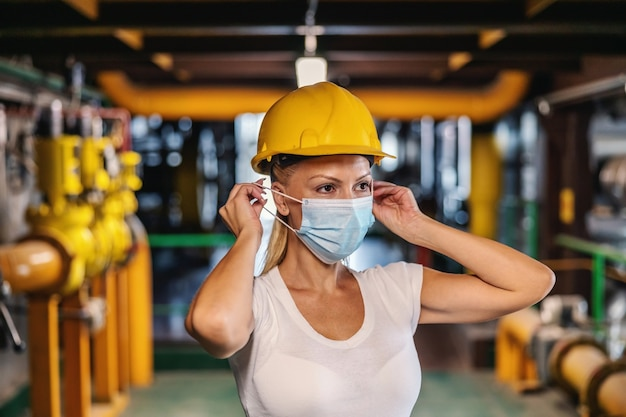Arbeiter mit helm auf dem kopf, der im heizwerk steht und während der korona schutzmaske aufsetzt.