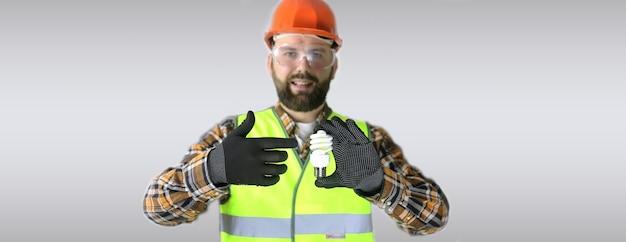 Arbeiter mit helm und schutzkleidung mit einer glühbirne in den händen