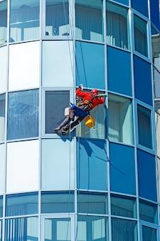 Arbeiter mit helm wäscht das fenster eines hochhauses von außen, das an einem seil hängt
