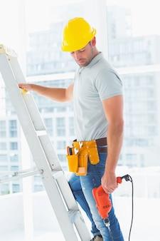 Arbeiter mit kletternder leiter der bohrgerätmaschine