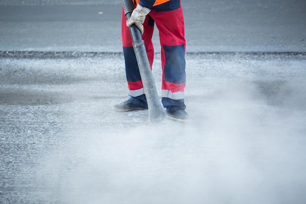 Arbeiter mit laubbläser, der den staub für eine bessere asphalthaftung entfernt, während der erneuerungsarbeiten der straßenbahnschienen