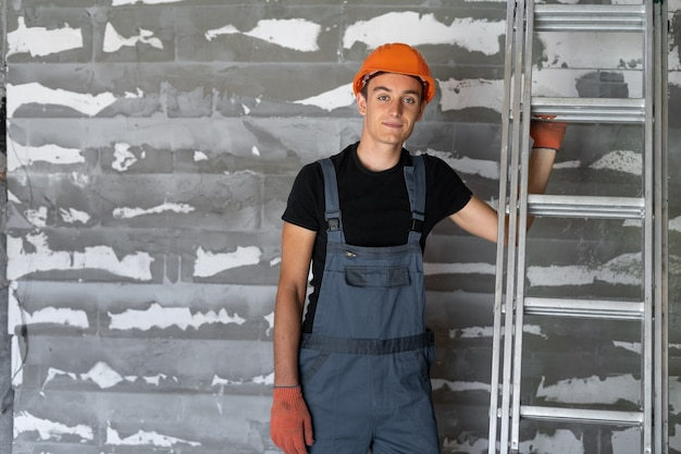 Arbeiter mit orangefarbenem helmhelm in der nähe einer steinmauer. es lohnt sich zu lächeln. platz kopieren.