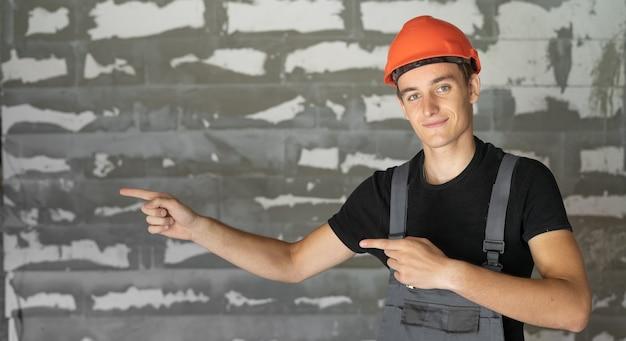 Arbeiter mit orangefarbenem helmhelm in der nähe einer steinmauer. mit zwei zeigefingern zeigt auf eine leere stelle für text.
