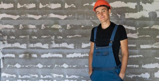 Arbeiter mit orangefarbenem helmhelm in der nähe einer steinmauer. vertrauliches lächeln. platz kopieren
