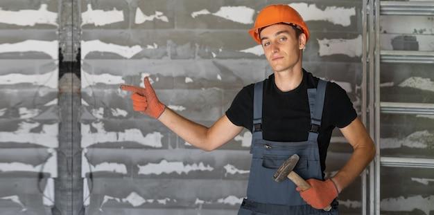 Arbeiter mit orangefarbenem helmhelm in der nähe einer steinmauer. zeigt mit dem finger auf eine leere textstelle.