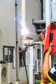Arbeiter mit schutzmaske funken beim schweißen von rohrleitungen