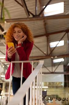 Arbeiter mit telefon. rothaariger schöner büroangestellter, der das telefon benutzt, während er eine kleine pause genießt