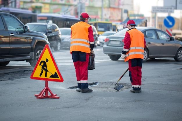 Arbeiter nivellieren asphalt auf der baustelle straßenreparatur