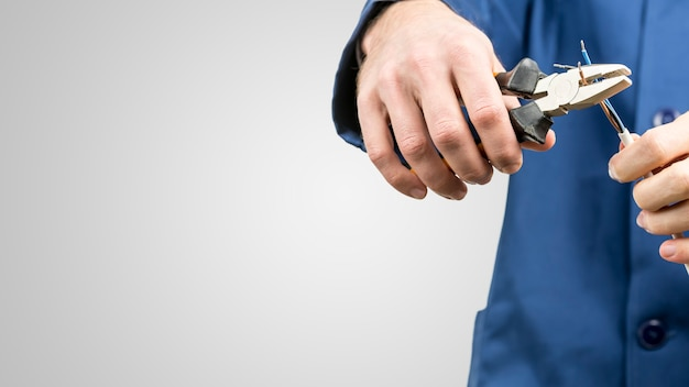 Arbeiter oder elektriker, der ein elektrisches kabel mit einer zange repariert, um die versorgung des hauses wiederherzustellen, nahaufnahme seiner hände in blauen overalls auf grau mit kopienraum