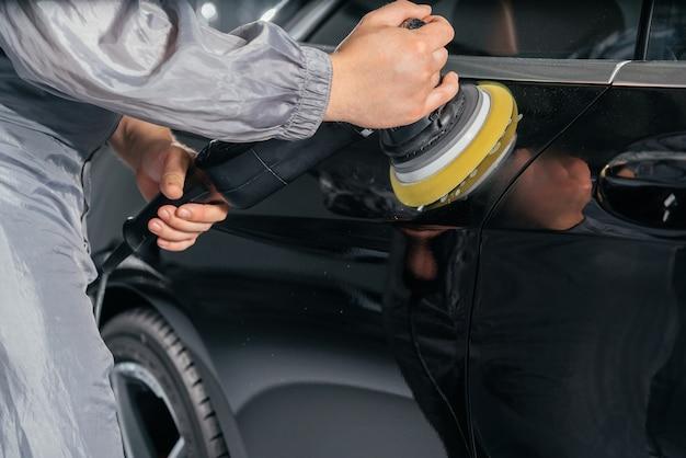 Arbeiter poliert auto mit spezialschleifer und wachs von kratzern an der autotankstelle. professionelles fahrzeugdetail- und wartungskonzept