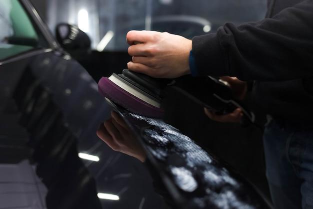 Arbeiter poliert die lackierung eines autos mit einem auto