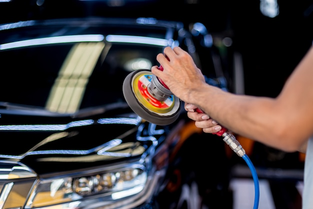 Arbeiter poliert ein auto mit einem elektrowerkzeug