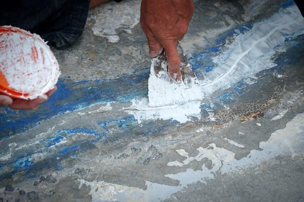 Arbeiter reparieren risse im boden putz mit kelle verteilen abdichtungsdeck reparieren