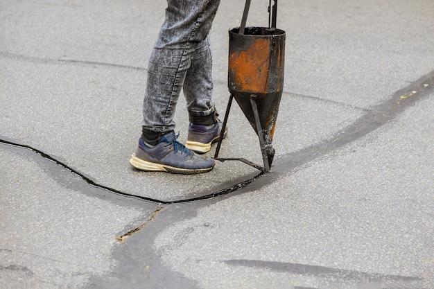 Arbeiter restaurierungsarbeiten versiegeln risse, indem sie flüssige versiegelung aufbringen, um eine straßenschutzbeschichtung auf der straße zu asphaltieren