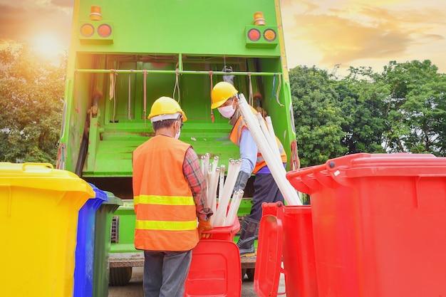 Arbeiter sammeln müll mit müllsammelwagen, müllsammelarbeiter im wohngebiet residential Premium Fotos