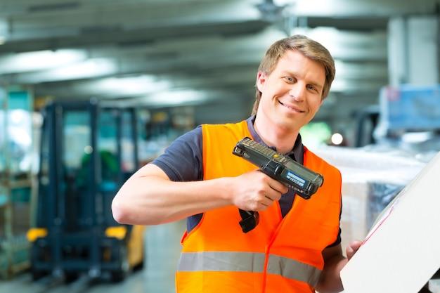 Arbeiter scannt paket im lager der spedition