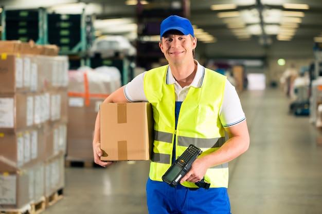 Arbeiter scannt paket im lager der weiterleitung