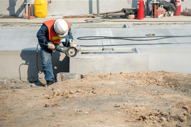 Arbeiter schneiden beton in der baustelle