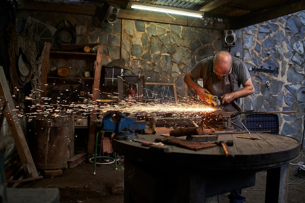 Arbeiter schneiden mit einer mühle in einer alten schmiede