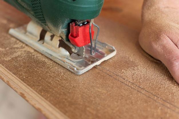 Arbeiter schneidet ein laminat einer bestimmten länge mit einer stichsäge