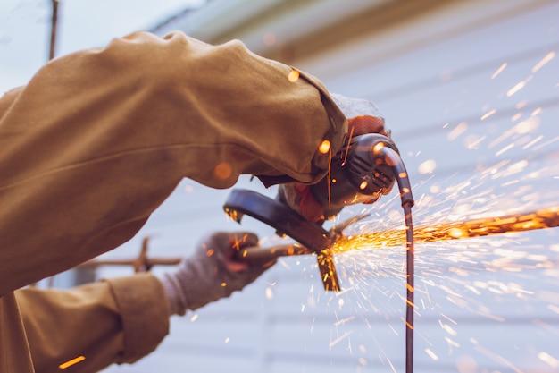 Arbeiter schneidet ein metallrohr mit einer mühle
