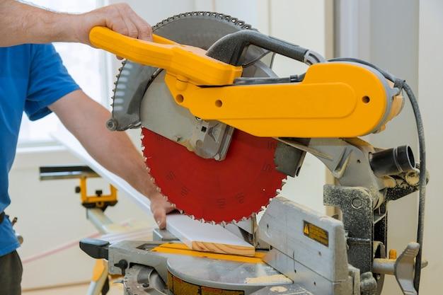 Arbeiter schneidet holzfußleiste auf der motorsäge rotierendes neues zuhause
