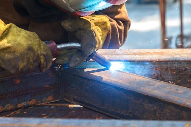 Arbeiter schweißen in einer fabrik. schweißen an einer industrieanlage.