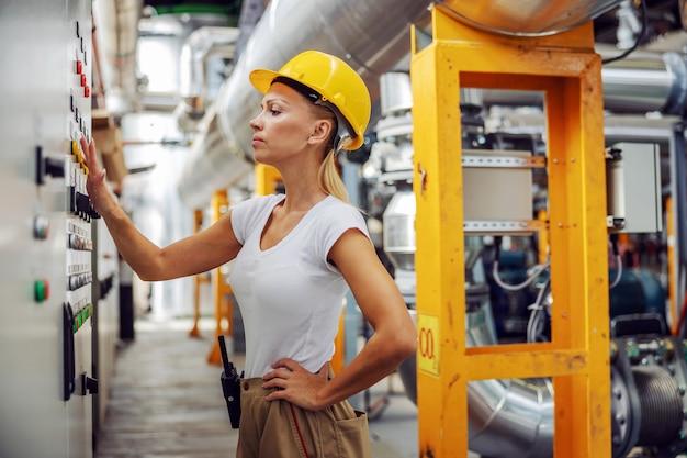 Arbeiter steht neben dem armaturenbrett im heizwerk und passt die einstellungen an