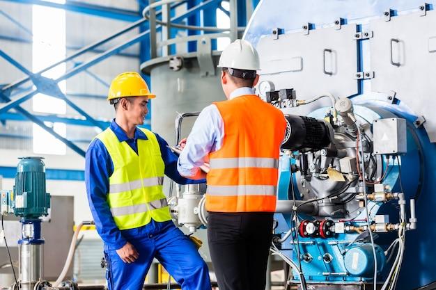 Arbeiter und manager in der industriefabrik diskutieren die akzeptanz der maschine